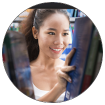 Woman browsing bookshelves - Finding Books for Your Nursing DNP Program Type